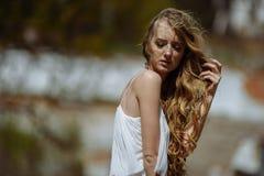 年轻人相当逗人喜爱的女孩室外夏天画象  摆在老桥梁的美丽的妇女 在站立近的石railin的白色dess 免版税库存图片