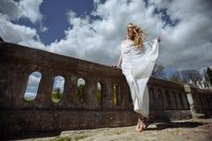 年轻人相当逗人喜爱的女孩室外夏天画象  摆在老桥梁的美丽的妇女 在站立近的石railin的白色dess 免版税库存照片