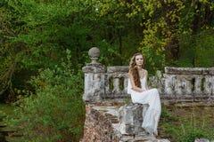 年轻人相当逗人喜爱的女孩室外夏天画象  摆在老桥梁的美丽的妇女 在选址在石栏杆附近的白色dess 免版税图库摄影