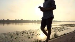 年轻人看他的智能手机并且对日落微笑对Dnipro 股票视频