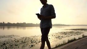 年轻人看他的智能手机并且对Dnipro微笑户外在Slo Mo 影视素材