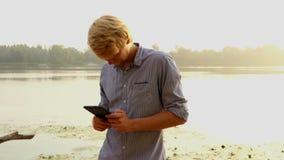 年轻人看他的智能手机并且对Dnipro微笑户外 股票视频
