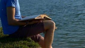 年轻人看在湖银行的照片 布朗鸭子附近游泳 股票录像
