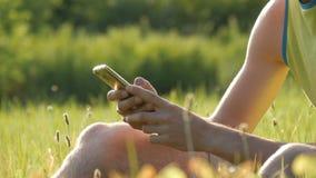 年轻人看智能手机,并且某事在绿草打印反对一个美好的夏天的背景 股票视频