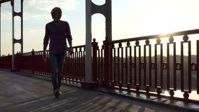 年轻人看Dnipro河,沿一座桥梁微笑并且去在Slo Mo 影视素材