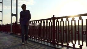 年轻人看Dnipro河,沿一座桥梁微笑并且去在Slo Mo 股票视频
