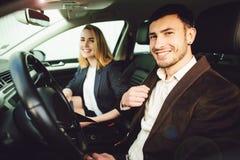 年轻人租用一辆汽车 经销商中心的雇员在汽车显示文件 库存图片