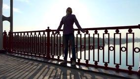 年轻人立场和微笑在一座桥梁的扶手栏杆附近在日落在Slo Mo 影视素材