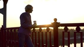 年轻人站立与一杯纸咖啡并且享用象在日落 股票视频