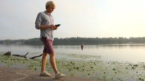 年轻人简而言之和一件衬衣有智能手机的沿河走 股票视频