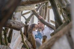 年轻人结合亲吻户外在木背景在乡下 库存照片