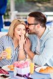 年轻人耳语秘密对他的女朋友 库存照片