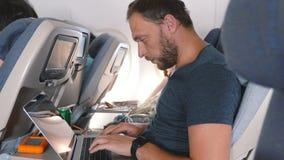 年轻人聚焦了与在网上运转在膝上型计算机移动式办公室的巧妙的手表的创造性的商人在平面飞行旅行期间 股票录像