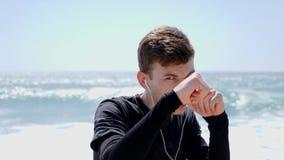 年轻人聚焦了与看对照相机的拳头的运动员拳击 佩带耳机的把装箱的锻炼 t 影视素材