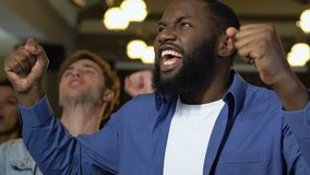 年轻人获得乐趣在酒吧,观看的足球比赛,欢呼为胜利 股票录像