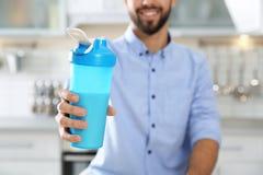 年轻人藏品瓶蛋白质震动在厨房里 免版税图库摄影