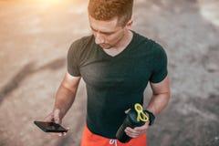 年轻人藏品瓶装水和电话 在夏天在运动场的城市 训练在互联网上的应用的检查 免版税库存照片