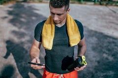 年轻人藏品瓶装水和电话 在夏天在运动场的城市 训练在互联网上的应用的检查 图库摄影