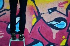年轻人街道画艺术家绘在墙壁上的一张新的街道画 得出在墙壁特写镜头的一张街道画的过程的照片 库存图片