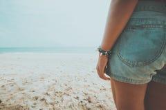 年轻人被晒黑的妇女身分在一个热带海滩放松 蓝色海在背景中 图库摄影