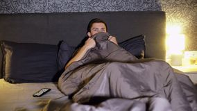 年轻人观看在电视的一恐怖电影,当在床上,害怕时并且盖他的面孔 影视素材