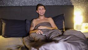 年轻人观看的喜剧在家 在床上的笑 人手表电视在家 影视素材