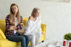 年轻人触犯了女同性恋的夫妇在家坐黄色沙发在争吵以后,穿便服 免版税图库摄影