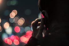年轻人谈话在手机在晚上 免版税库存照片