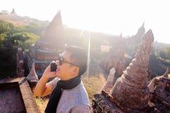 年轻人谈话在电话在农村和寺庙塔区域- 免版税库存图片