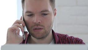 年轻人谈话在电话,当研究膝上型计算机时 股票录像