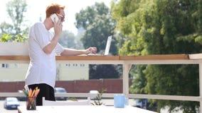 年轻人谈话在电话,站立在室外的阳台上 库存照片