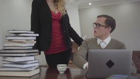 年轻人谨慎地打扮了玻璃的人在家在桌上,工作坐膝上型计算机 有深的美女 股票录像
