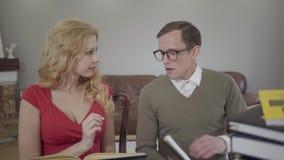 年轻人谨慎地打扮了读书的玻璃和卷曲白肤金发的妇女的人坐沙发 书呆子落 影视素材