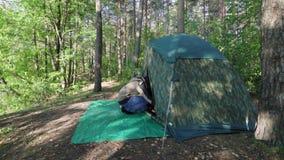 年轻人走向旅游伪装帐篷在森林游人的黎明有长的头发的离开他的鞋子输入  影视素材