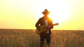 年轻人走在日落的光芒的金黄麦田与吉他的 股票录像