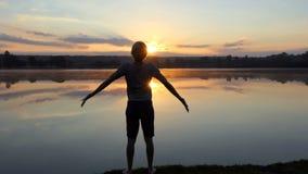年轻人跑到森林湖在精采日落在slo mo 影视素材