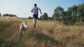 年轻人跑户外与他的拉布拉多 跑步与他的宠物一起的人本质上 家畜跟随它 股票视频