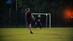 年轻人跑由球决定,踢它往目标,但是守门员敲打球, shooring的夜 股票录像