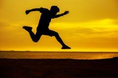 年轻人跳在太阳和通过在平衡五颜六色的天空的小山剪影空白 免版税库存照片