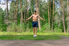 年轻人跳绳在杉木森林里 库存照片