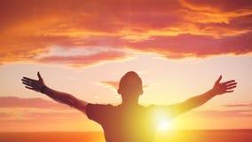 年轻人身分被伸出在日落 明亮的太阳焕发和天空 免版税库存照片