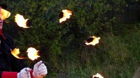 年轻人转动两个金属爱好者与火焰在他自己附近在Slo Mo 它是不可思议的 股票视频