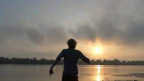 年轻人转过来与在旁边手在河岸在日落在Slo Mo 影视素材