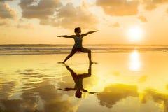 年轻人适合剪影和健康可爱的女子实践的健身和瑜伽在美好的日落在凝思靠岸并且放松 免版税库存照片