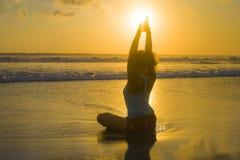 年轻人适合剪影和海滩日落瑜伽的可爱的体育妇女在med实践锻炼坐在海前面的湿太阳 库存图片