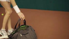 年轻人适合的妇女的腿特写镜头视图有一个袋子和网球拍和的为在法院的训练做准备 股票录像