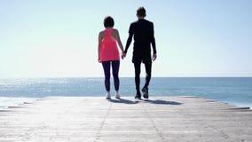 年轻人适合的白种人男人和妇女举行手,当走到海时 t 影视素材