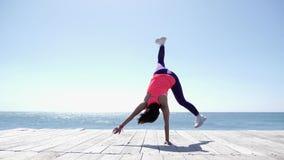 年轻人适合的运动妇女做在海滩的车轮 击中海岸慢动作的强的波浪 股票录像
