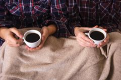 年轻人递两个杯子热的格子花呢披肩女性人咖啡衬衣笼子 库存照片