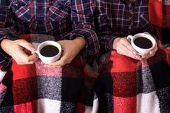 年轻人递两个杯子热的格子花呢披肩女性人咖啡衬衣笼子 免版税库存照片